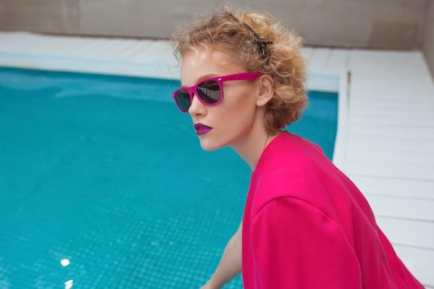 Stylowa rudowłosa, kręcona młoda kobieta siedząca przy basenie