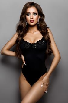 Stylowa seksowna dziewczyna w czarnym stroju kąpielowym na białym tle na szarym tle