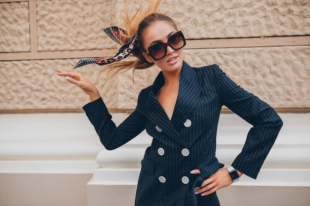 Stylowa seksowna kobieta ubrana w elegancki garnitur spaceru po mieście w letni wiosenny dzień