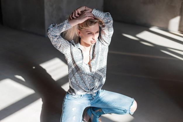 Stylowa seksowna młoda blond kobieta w vintage letniej koszuli w modne niebieskie dżinsy zgrywanie w zielonych kowbojskich butach, pozowanie, siedząc w pomieszczeniu z promieniami słonecznymi