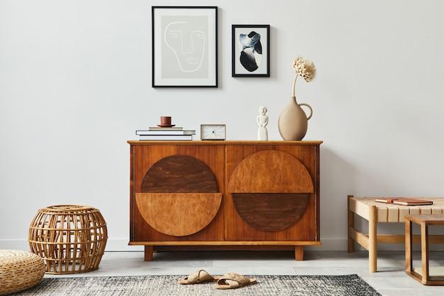 Stylowa skandynawska kompozycja salonu z designerską komodą, czarnymi ramami na plakaty, rattanową pufą, zegarem, drewnianym stołkiem, książką, dekoracją i osobistymi akcesoriami w nowoczesnym wystroju domu.