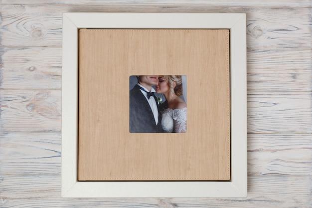 Stylowa skrzynka dla fotoksiążek .. karton na rodzinnym albumie fotograficznym. pudełko z ślubnym albumem fotograficznym z copyspace. skórzana fotoksiążka ślubna w pudełku.