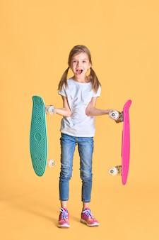 Stylowa śmieszna dziewczyna ubrana w biały t-shirt, niebieskie dżinsy i trampki, trzymająca dwie deskorolki na żółtej ścianie