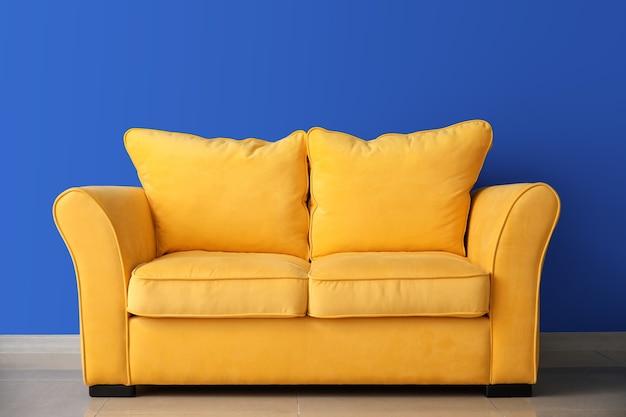 Stylowa sofa w pobliżu kolorowej ściany w pokoju