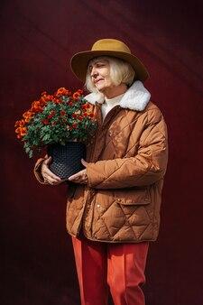 Stylowa starsza pani z doniczką. zadowolona starsza kobieta niosąca doniczkę z kwitnącymi kwiatami