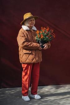 Stylowa starsza pani z doniczką. zadowolona starsza kobieta w modnym kapeluszu niosąca doniczkę z kwiatami