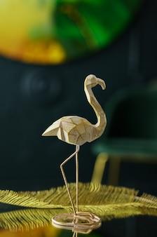 Stylowa statuetka flaminga i dekor na lustrzanym stoliku kawowym w secesyjnym wnętrzu, w kolorach złotym i ciemnozielonym. nowoczesny zielony salon - wystrój domu