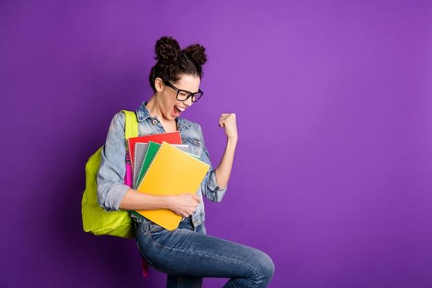 Stylowa studentka z kręconymi włosami, pozująca na fioletowej ścianie
