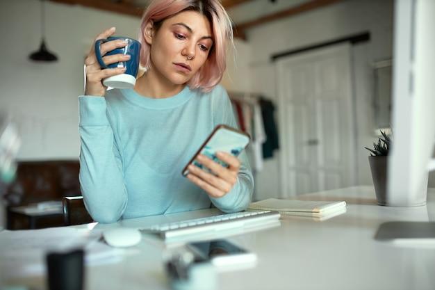 Stylowa studentka z różowymi włosami i kółeczkiem w nosie siedzi przy stole z kubkiem i telefonem komórkowym, pije kawę i przegląda wiadomości za pośrednictwem swojego konta w mediach społecznościowych rano, pisze do znajomych online
