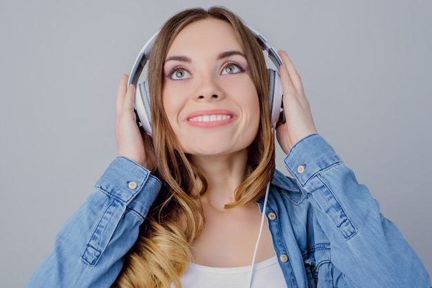 Stylowa stylowa casualowa stylistyka dźwiękowa ząbkowana melodia. bliska portret uroczej pięknej podekscytowanej radosnej marzycielskiej uroczej dziewczyny dotykającej białych słuchawek z rozpromienionymi rękami na białym tle na szarej ścianie