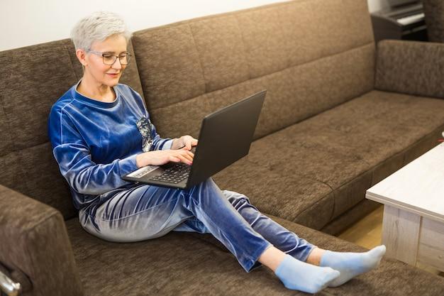 Stylowa stylowa kobieta z krótką fryzurą z laptopem w domu