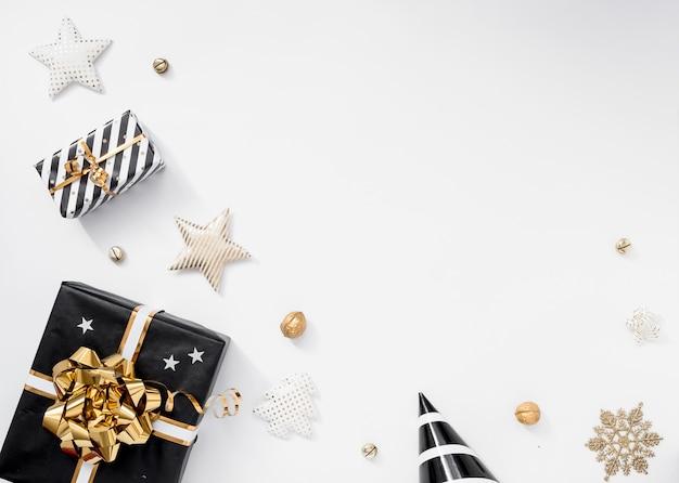 Stylowa świąteczna dekoracja. prezenty, kapelusze, czarne i złote dekoracje na białym tle