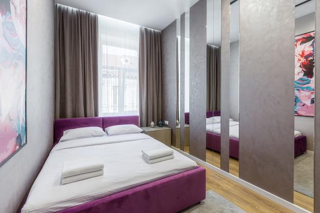 Stylowa sypialnia z dużym łóżkiem, nowoczesne wnętrze, projekt pokoju z lustrami, aby zwiększyć przestrzeń