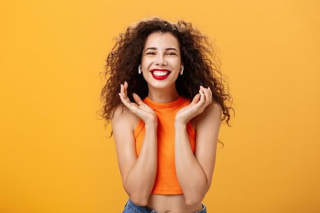 Stylowa, szczęśliwa, atrakcyjna miejska kobieta z kędzierzawą fryzurą i kolczykiem w nosie, uśmiechnięta szeroko czując się zachwycona, słuchając ulubionego utworu w bezprzewodowych słuchawkach, unosząc dłonie w pobliżu twarzy pozującej nad pomarańczową ścianą.