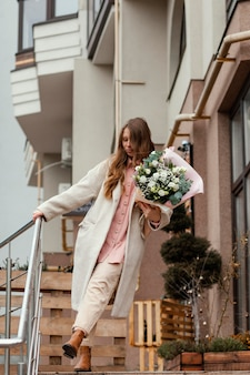 Stylowa szczęśliwa kobieta trzyma bukiet kwiatów na zewnątrz w mieście