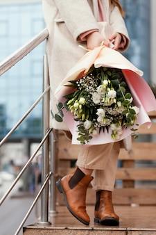 Stylowa szczęśliwa kobieta trzyma bukiet kwiatów na zewnątrz