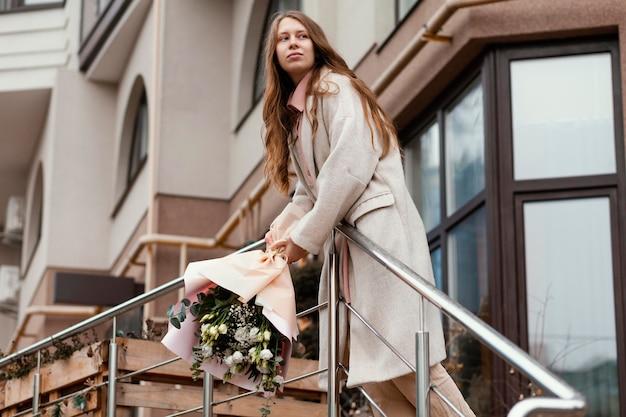 Stylowa szczęśliwa kobieta trzyma bukiet kwiatów w mieście
