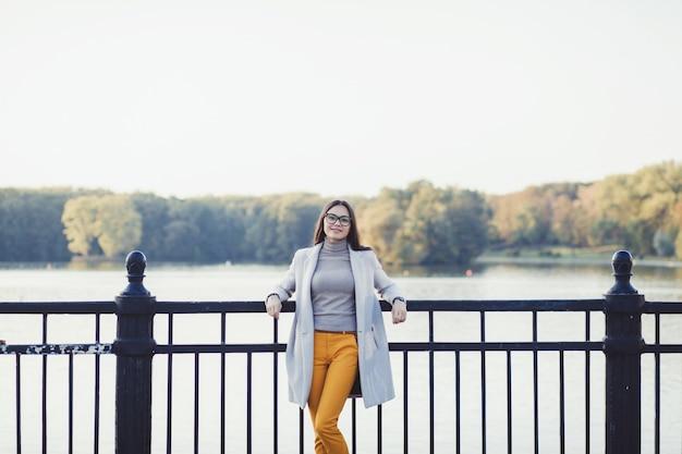Stylowa szczęśliwa kobieta w jesienny płaszcz rzeki w parku