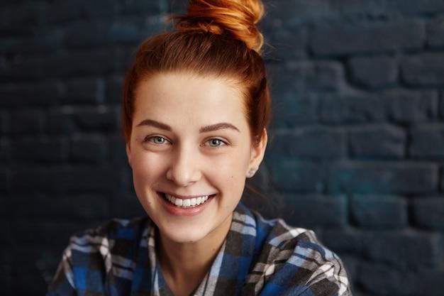 Stylowa szczęśliwa młoda europejska kobieta z rudymi włosami i czarującym uśmiechem patrząc