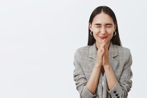 Stylowa szczęśliwa młoda kobieta o ciemnych włosach w marynarce, zamykająca oczy i uśmiechająca się radośnie, trzymając się za ręce do modlitwy i mając nadzieję na lepsze