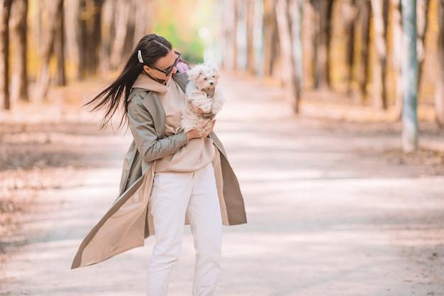 Stylowa szczęśliwa młoda kobieta w dżinsach, białe trampki chodzenie z białym szczeniakiem