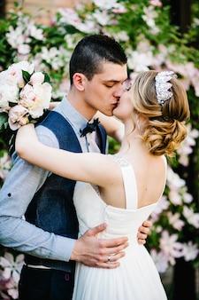 Stylowa szczęśliwa panna młoda z bukietem piwonii z koroną i pana młodego.