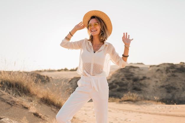 Stylowa szczęśliwa piękna uśmiechnięta kobieta pozuje w piasku pustyni w białym stroju na sobie słomkowy kapelusz i okulary przeciwsłoneczne na zachód słońca