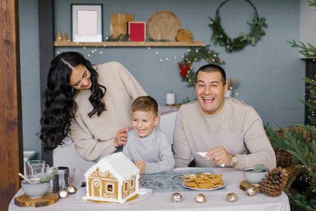 Stylowa szczęśliwa rodzina dekoruje domek z piernika