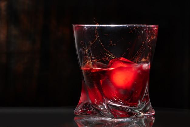 Stylowa szklanka z brandy i kostkami lodu z bliska
