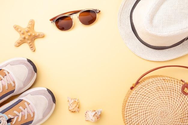 Stylowa torba rattanowa, gałęzie monstera, okulary przeciwsłoneczne, trampki, czapka na żółtym tle.