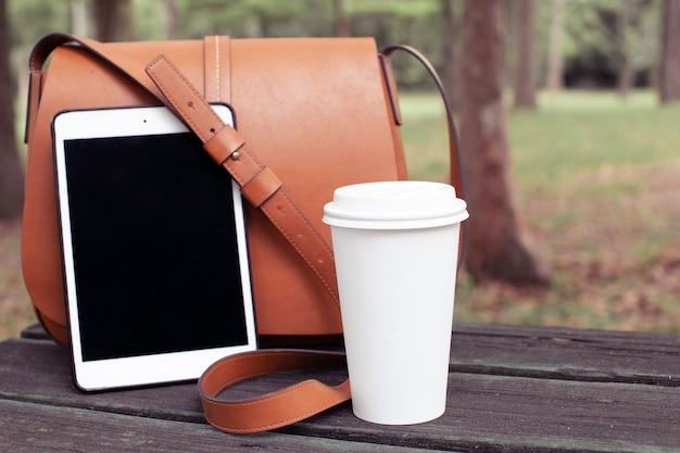 Stylowa torebka damska filiżanka kawy herbaty i podkładki na drewnianym stole w koncepcji stylu życia w parku