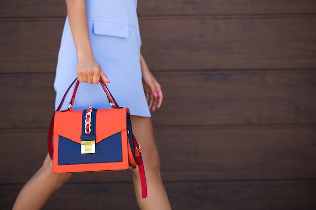 Stylowa torebka damska w kolorze niebieskim z pomarańczową skórą. dziewczyna trzyma w dłoni. torba z bliska. zbliżenie.