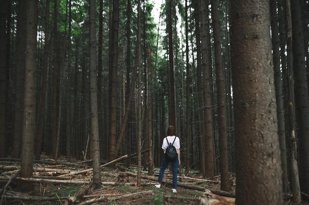 Stylowa turystka kobieta stojąca w środku górskiego lasu jodłowego, patrząc daleko w przyszłość