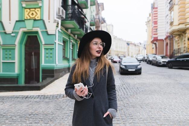 Stylowa turystka spacerująca ulicami starego miasta i uśmiechnięta. dziewczyna spaceruje ulicami