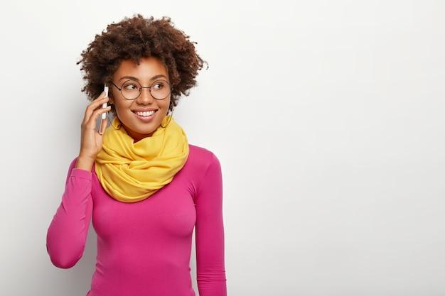Stylowa tysiącletnia dziewczyna o ciemnej karnacji, do komunikacji używa gadżetu smartfona