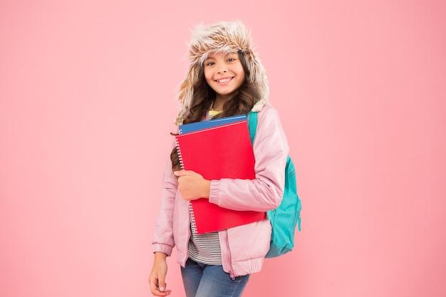 Stylowa uczennica. dziewczyna mała modna uczennica nosi plecak. codzienne życie uczennicy. nowoczesna edukacja. egzaminy końcowe. dzień przybycia. termin akademicki. semestr zimowy. nastolatek z plecakiem i książkami.