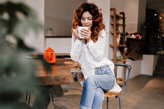 Stylowa urocza młoda dama ubrana w białą koszulę i dżinsy, siedząc w przytulnej kawiarni, pijąc smaczną kawę i relaksując się po pracy
