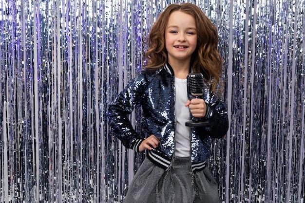 Stylowa uśmiechnięta dziewczyna z mikrofonem retro w dłoni na błyszczącej wakacyjnej ścianie