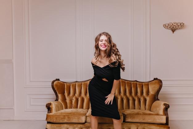 Stylowa, uśmiechnięta, fantastyczna młoda kobieta radosna i wesoła pozuje do pełnometrażowego zdjęcia na tle welurowej klasycznej sofy