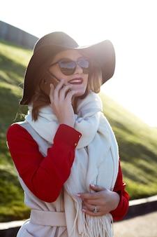 Stylowa uśmiechnięta kobieta w kapeluszu i okularach rozmawiająca przez telefon komórkowy w parku