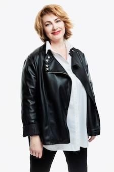 Stylowa uśmiechnięta kobieta w średnim wieku w białej koszuli i skórzanej kurtce na białej ścianie. zdrowy styl życia i aktywność. pionowy.