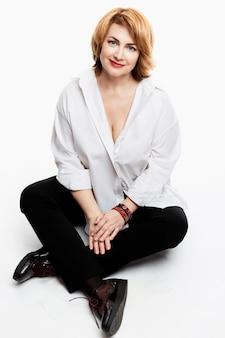Stylowa uśmiechnięta kobieta w średnim wieku w białej koszuli siedzi na białej ścianie. zdrowy styl życia i aktywność. pionowy.
