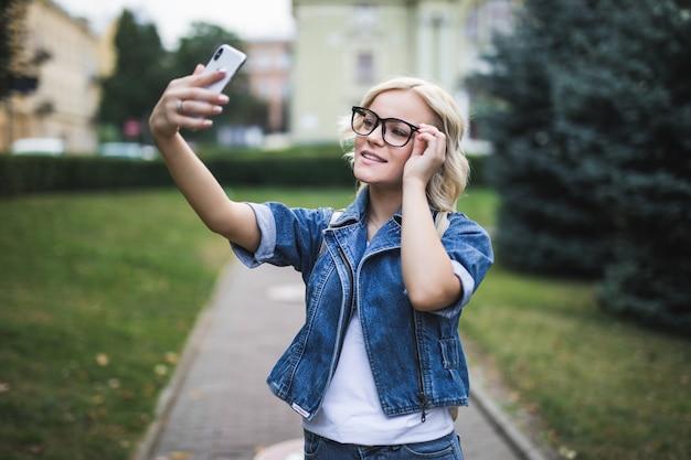 Stylowa uśmiechnięta moda blondynka kobieta w dżinsach suite sprawia, że selfie na swoim telefonie w mieście rano