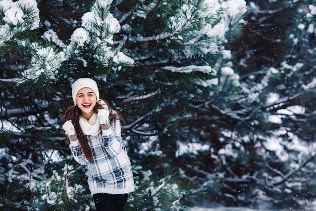 Stylowa wesoła dziewczyna w swetrze w zimowym lesie.