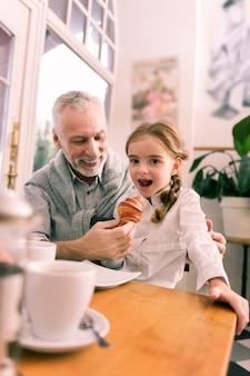 Stylowa wnuczka. śliczna stylowa wnuczka w białej koszuli próbuje rogalika jedzącego śniadanie z dziadkiem