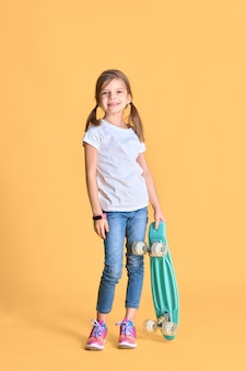 Stylowa zabawna dziewczyna ubrana w biały t-shirt, niebieskie dżinsy i trampki, trzymająca deskorolkę na żółtej ścianie