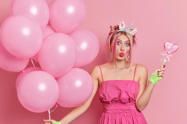 Stylowa zaskoczona europejka zagina usta bawi się na przyjęciu urodzinowym z pysznymi cukierkami, a pęk napompowanych balonów ma świetny nastrój