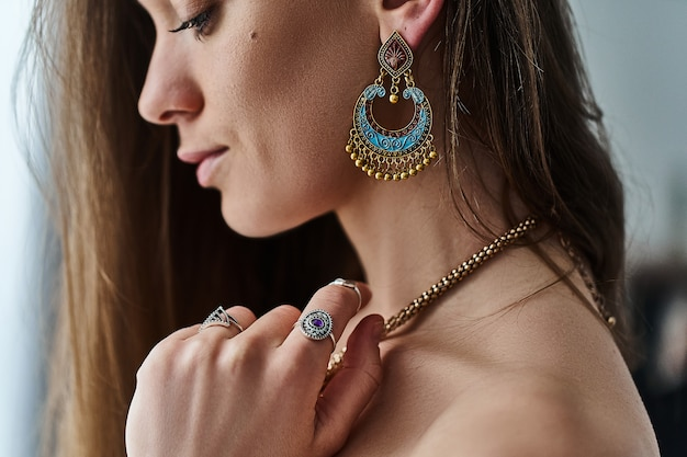 Stylowa zmysłowa kobieta w stylu boho, ubrana w duże kolczyki, złoty naszyjnik i srebrne pierścionki z kamieniem. modny cygański cygański indyjski strój z detalami z biżuterii