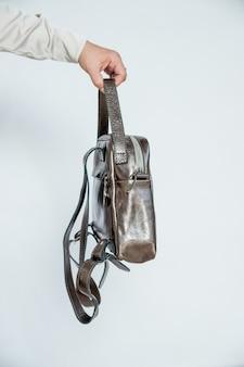 Stylowe akcesoria na białym tle. torebka w kolorze brązowym w kobiecej dłoni