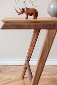 Stylowe beżowe wnętrze nowoczesnej jadalni z designerskim drewnianym dębowym stołem i krzesłami, wazonem z kwiatami, eleganckimi rattanowymi dodatkami i dekoracją. koreański styl wystroju domu. szablon.